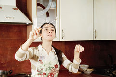 Woman conducting in kitchen Royalty Free Stock Photography