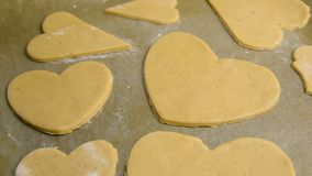 Woman confectioner cuts out hearts from the dough for baking gingerbread. To the St. Valentine`s Day stock footage