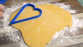Woman confectioner cuts out hearts from the dough for baking gingerbread. To the St. Valentine`s Day stock video footage
