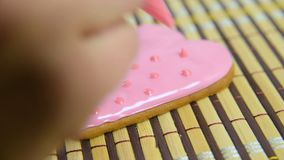 Woman confectioner decorates and decorates the glaze with gingerbread cookies in the shape of heart. Valentine`s Day, February 14, symbol, valentine, gift stock footage