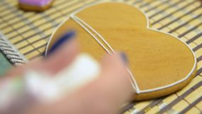 Woman confectioner decorates and decorates the glaze with gingerbread cookies in the shape of heart. Valentine`s Day, February 14, symbol, valentine, gift stock video