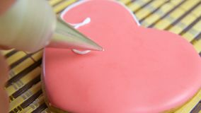 Woman confectioner decorates and decorates the glaze with gingerbread cookies in the shape of heart. Valentine`s Day, February 14, symbol, valentine, gift stock video footage