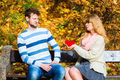 Woman confess love to man on bench in park. Confessing love and affection with romantic gesture. Rejection and disapproval. Negative reaction. Pair sit on bench Royalty Free Stock Photography