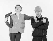 Woman with confident face in helmet, hard hat holds drill. Near mouth, lips, white background. Confident builder, repairman shows thumb up gesture near lady stock images