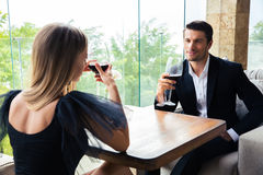 Woman and confident man drinking red wine Stock Image