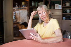 Woman confused with tablet computer Royalty Free Stock Photography