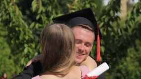 Woman congratulating graduate boyfriend and embracing him, happy moment stock video