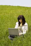 Woman connected on the grass. Blonde woman connected to the internet in a meadow Royalty Free Stock Photography