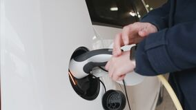 Woman connecting power supply to electric vehicle for charging and blocks car using smart watch.