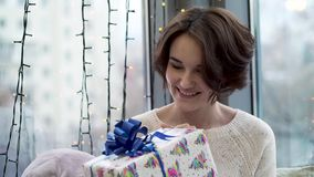 Woman considering new year gift. Beautiful young woman in sweater with smile and curiosity is considering Christmas gift. New year and Christmas holidays stock video footage