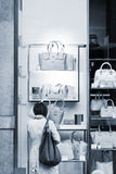 Woman considers bags in a show-window of boutique Stock Photography