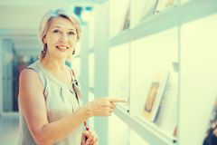 Woman considers the book in a bookstore. Mature woman coners the book in a bookstore stock photos
