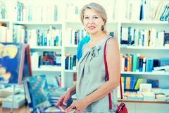 Woman considers the book in a bookstore. Mature woman coners the book in a bookstore royalty free stock images