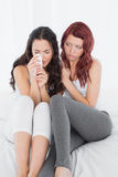 Woman consoling a crying female friend on bed Stock Photos