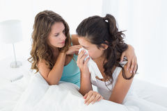 Woman consoling a crying female friend in bed Royalty Free Stock Photos