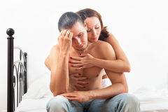 Woman consoling the depressed man in bedroom at home Stock Images
