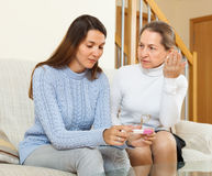 Woman consoling the worried daughter. Mature women  consoling the worried teen daughter with pregnancy test at home Royalty Free Stock Photos
