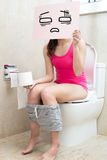 Woman with constipation. Woman take confuse billboard with constipation in the bathroom Royalty Free Stock Photography