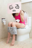 Woman with constipation. Woman take confuse billboard with constipation in the bathroom Royalty Free Stock Images