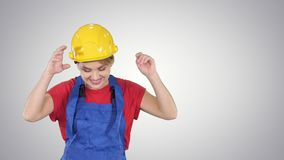Woman in construction helmet dancing on gradient background. stock video footage