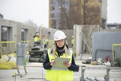 Free Woman Construction Site Engineer Architect Worker With Hard Hat Writes Notes Stock Photography - 216997112