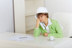 Woman - construction superintendent sits upset. The woman the construction superintendent sits upset for a table royalty free stock photography