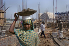 Woman construction worker. An Indian rural woman construction worker is carrying a bucket of material on her head Stock Photos