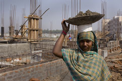 Woman construction worker. An Indian rural woman construction worker is carrying a bucket of material on her head Royalty Free Stock Photography