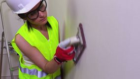 Woman construction worker grind the wall stock video