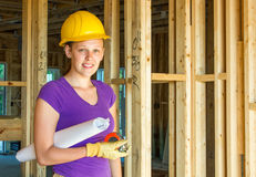 Woman construction worker holding architectural drawings Royalty Free Stock Photo