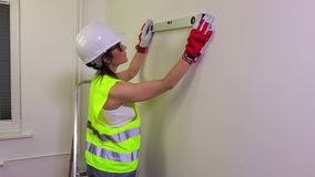 Woman construction worker with spirit level near wall stock footage
