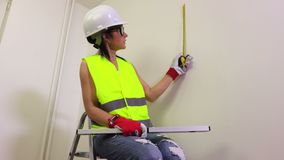 Woman construction worker using tape measure stock footage