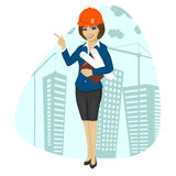 Woman construction worker wearing hard hat holding blueprints and clipboard pointing Royalty Free Stock Image