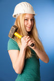 Woman with constructor helmet and hammer happy to do tough work. Stock Photography