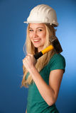 Woman with constructor helmet and hammer happy to do tough work. Stock Images