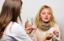Woman consult with doctor. Girl in scarf examined by doctor. Cold and flu remedies. Doctor communicate with patient. Recommend treatment. Doctor ask patient stock images