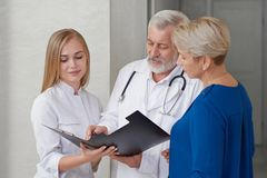 Consultation of two doctors and woman in hospital. royalty free stock photography