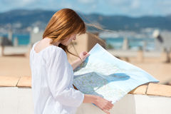 Woman consulting a map on an urban rooftop Stock Image
