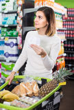 Woman consulting shopping list in supermarket. Young russian woman consulting shopping list in supermarket Royalty Free Stock Photo