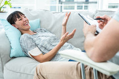 Woman consulting a therapist. In the clinic and therapist writing down his notes Stock Photo