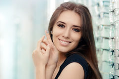 Woman with Contact Lenses Case in Optical Store. Beautiful girl holding contact lens container in optician shop Royalty Free Stock Photo