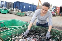 Woman at container cables in salvage yard Stock Photo