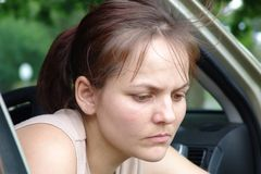 Woman Contemplating. Woman sits in a car comsumed by her thoughts Royalty Free Stock Image