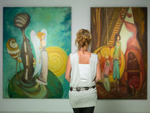 Woman contemplating colorful paintings Royalty Free Stock Image