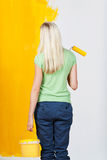 Woman contemplating a half painted wall Royalty Free Stock Photo