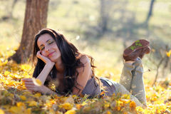 Woman contemplating in leafs. Happy young woman laying on the ground and meditating Royalty Free Stock Images