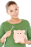 Woman contemplating opening her piggy bank Stock Photos