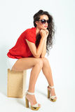 Woman contemplating while sitting on a chair, wearing sunglasses Stock Image