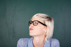 Woman Contorting Her Face Against Chalkboard Stock Photo