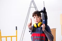 The woman contractor with hand drill at construction site royalty free stock photography